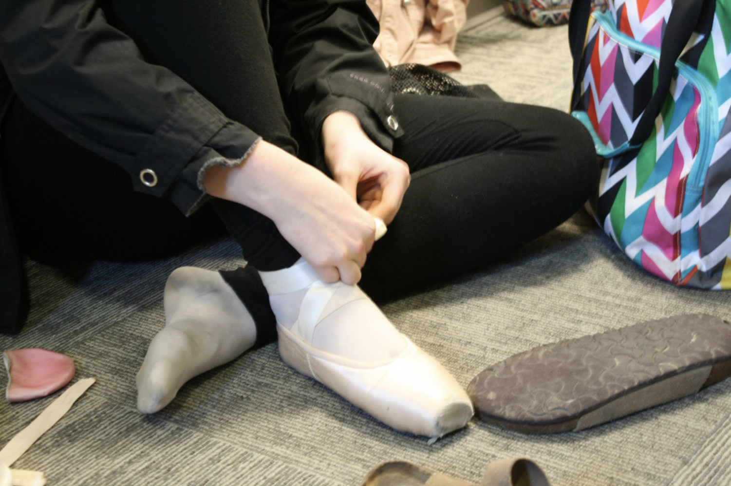 Elizabeth Arnold, 9, laces her pointe shoes. Photo by Kylie Heagy