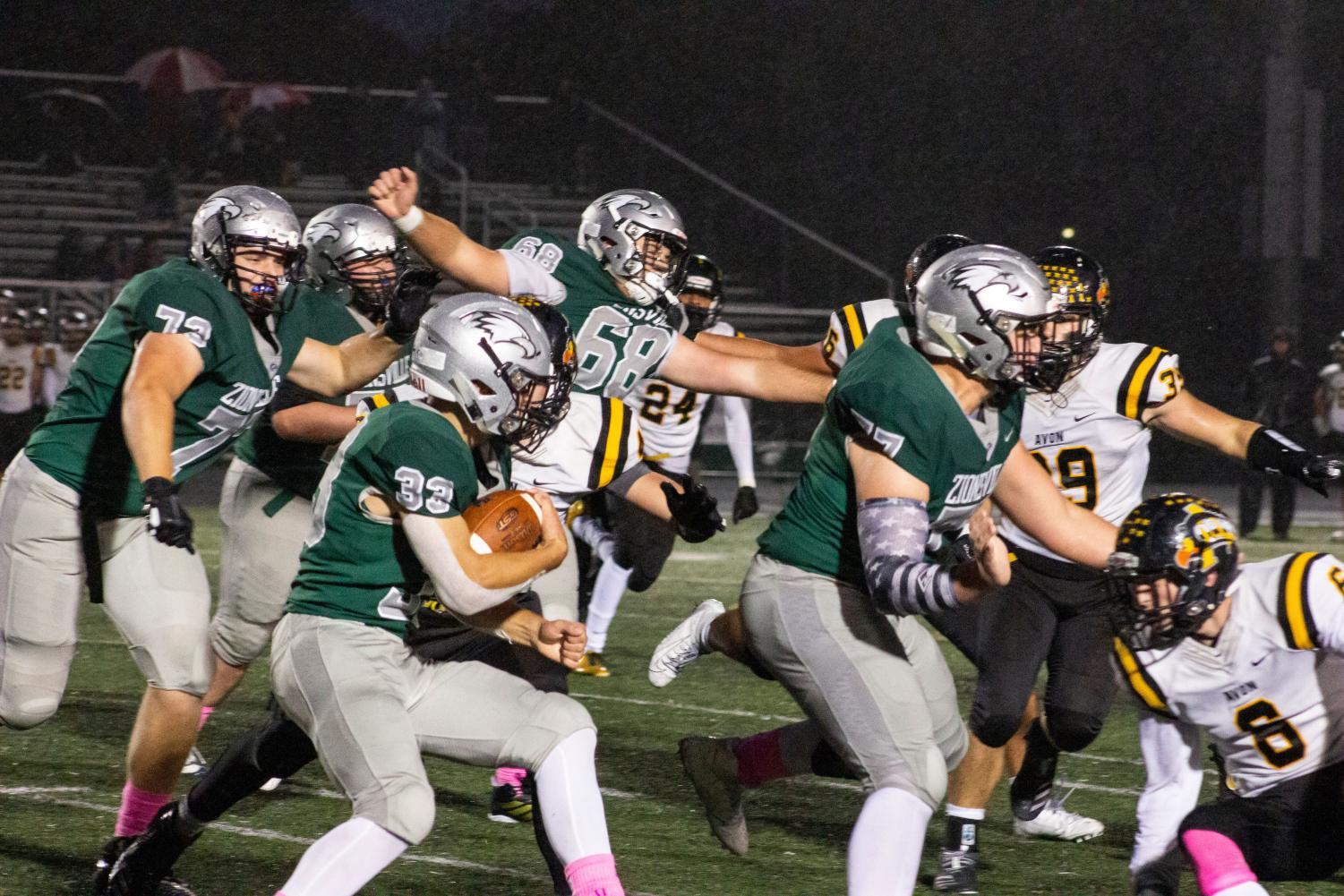 Gus Hartwig, senior, blocks multiple defenders during a play where Sophomore Colin Price runs the ball down the field.